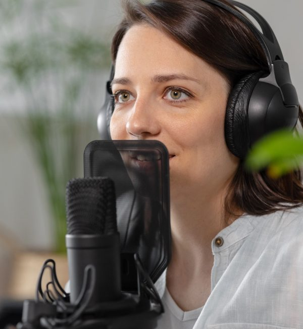 a-caucasian-millennial-woman-with-a-microphone-and-headphones-records-a-podcast-in-a-recording-studio_t20_pLk381