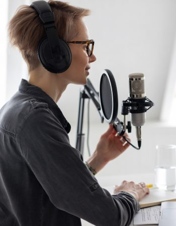 beautiful-european-woman-with-short-hair-in-glasses-smiles-and-records-a-podcast-holds-a-microphone_t20_azP8v9